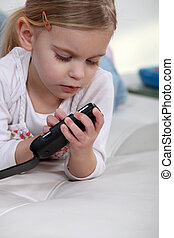 Little girl playing with mobile telephone
