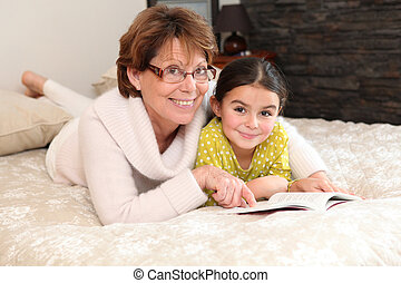 little girl reading a book with her granny