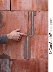 Man pointing out problem with wall