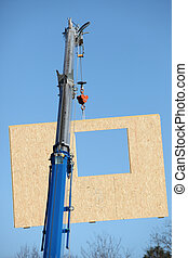 Crane lifting a section of wooden wall