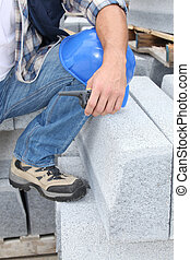 Construction worker kneeling by concrete blocks