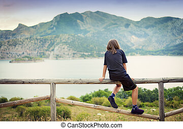 Child looking at a landscape - Mountains, lake and boy...