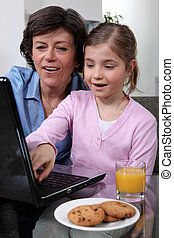 Young child looking at a laptop with her grandmother