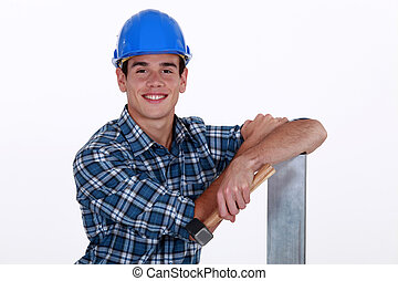 Builder with hammer and sheet of metal