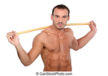 bare-chested man showing off with stick against white...