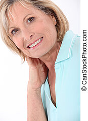 mature blonde woman wearing a turquoise polo shirt having a...