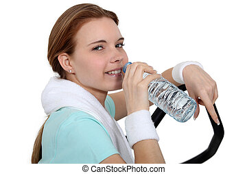 Woman drinking water during a workout