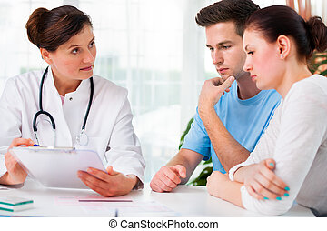 Doctor consults a young couple - doctor woman offering...