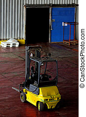 Yellow forklift parked in a modern wharehouse