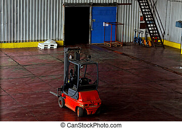 Red forklift parked in a modern wharehouse