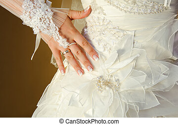 Hand of bride with a wedding ring on her dress