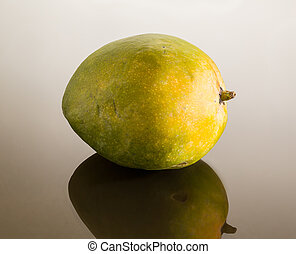 Green mango on mirror like surface - One whole round mangoes...
