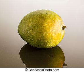 Green mango on mirror like surface - One whole round mangoes...