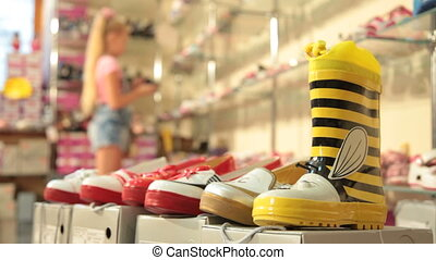 Choosing Footwear in Shoe Store - Little girl choosing...