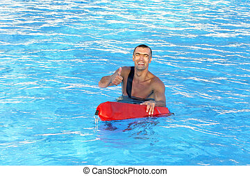 Posing lifeguard - Athletic lifeguard posing in swimming...