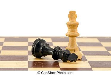 Black chess king lie near winner white legs