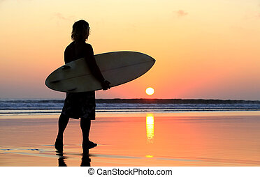 Surfer on sunset - Silhouette of surfer at red sunset Kuta...