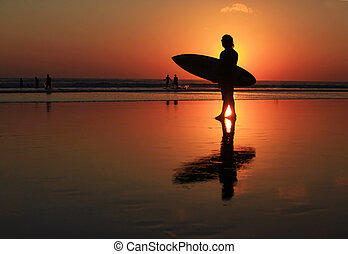 Surfer on sunset - Silhouettes of surfer at red sunset. Kuta...