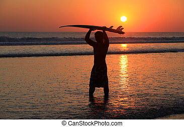 Surfer on sunset - Silhouettes of surfer at red sunset Kuta...