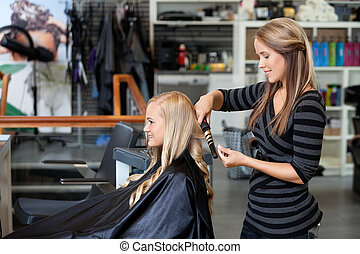 Woman Getting a New Hairstyle - Side view of young stylist...