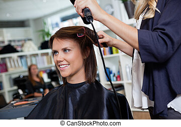 Woman At Parlor - Happy young woman getting her hair set by...