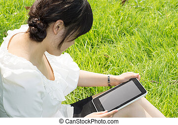 Tablet PC a woman - girl using tablet pc on the grass