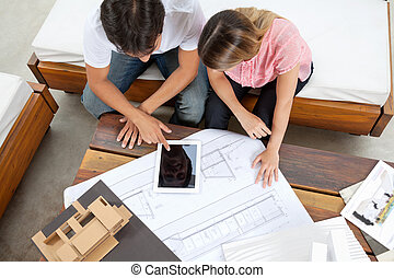 Couple With House Plans - High angle view of couple using...