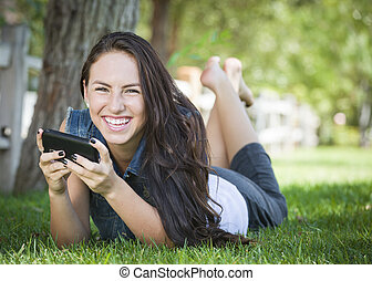 Mixed Race Young Female Texting on Cell Phone Outside -...