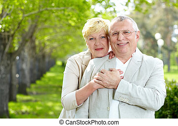Togetherness - Portrait of happy mature woman hugging her...