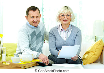 Counting family budget - Portrait of mature man and his wife...