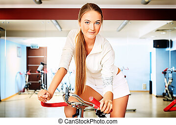 well being - Young sporty woman doing exercise on bicycle in...