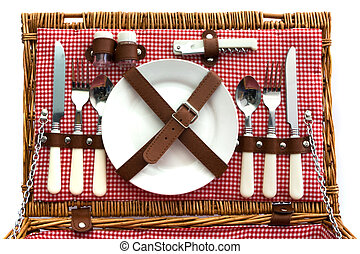 Old fashioned wicker picnic basket with cutlery