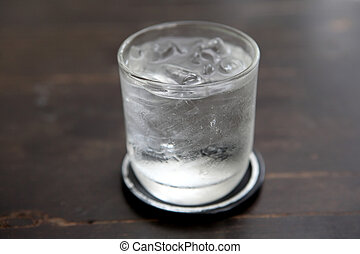 Glass with water on wood background