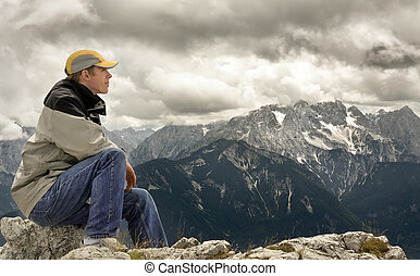 Enjoying the view from the mountain top - Young man sitting...