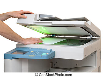 Working with a copier - Hands putting a sheet of paper into...