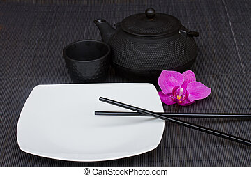 asian food concept - empty plate with chopsticks and tea set