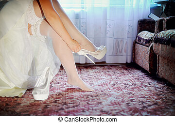 the bride puts on - beautiful legs of the bride in white...