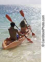 couple paddling their kayak in hawaii