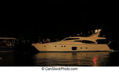A yacht in a quay - A yacht sailing near a quay at night