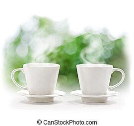 Cups of hot drink on defocus summer background