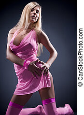 The beautiful sexual blonde in a pink transparent dress in...