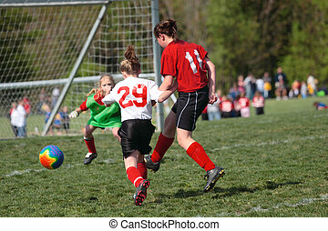 Youth Soccer Play - Youth Girl soccer player kicking ball...