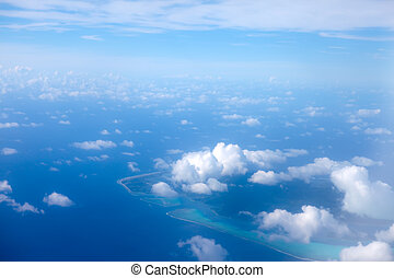 The atoll ring at ocean is visible through clouds. Aerial view.