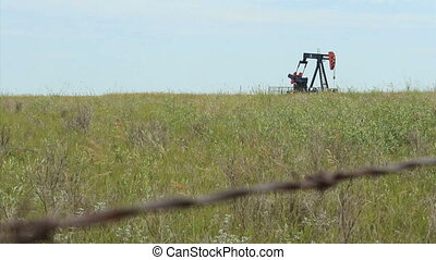 Oil Pump Behind Barbed Wire - A lonely oil pump works...