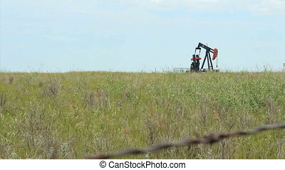 Oil Pump In Field - A lonely oil pump works tirelessly on...