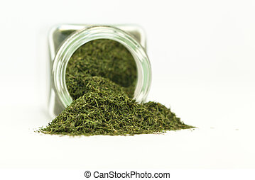 Dried dill weed spilling out of a clear glass jar