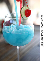 Blue cocktail with cherry and lime , kamikaze