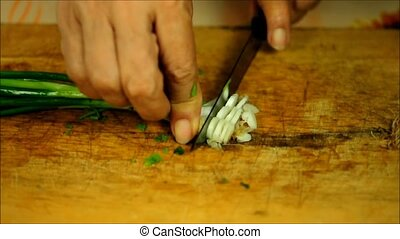 The green part of spring onions being cut into rings
