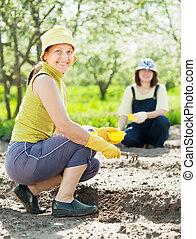 women works at  garden in spring