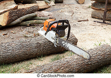 Timber - Chainsaw at heap of logs in a forest